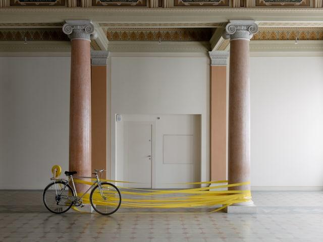 An zwei Säulen gelehnt steht ein Fahrrad, dahinter ist gelbes Band um die Säulen gewickelt.