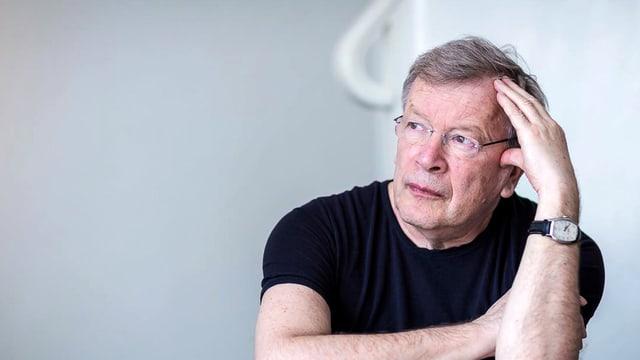 Viktor Jerofejew, mit randloser Brille und aufgestütztem Kopf, sitzend.