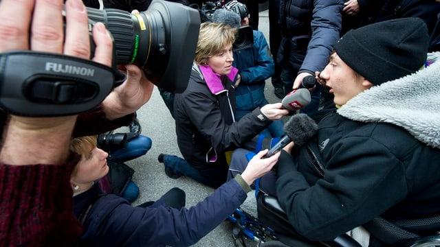 Luca im Rollstuhl von Journalisten umringt.