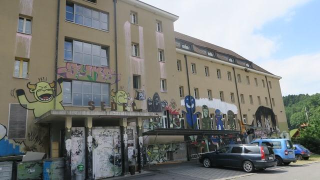 Aussenansicht eines ehemaligen Gefängnisses. Aussenfassade ist besprayt.
