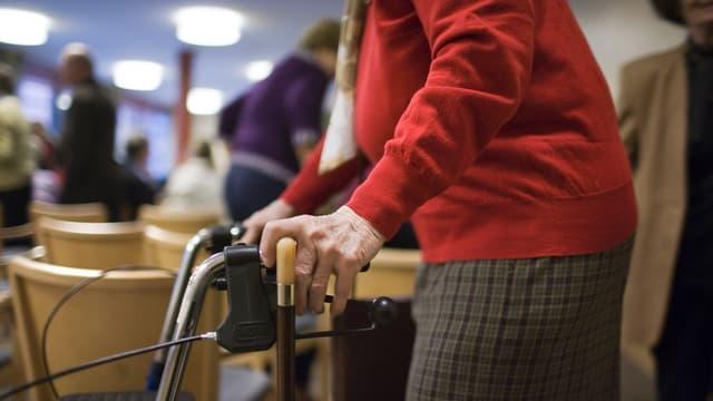 Eine alte Frau in rotem Pullover stösst eine Gehhilfe.