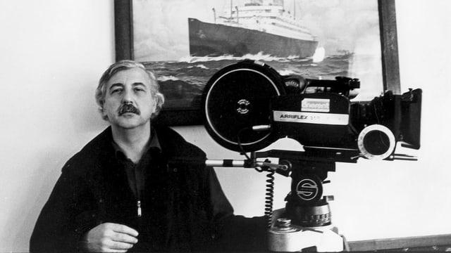 Ein Mann mit Schnauz sitzt neben einer grossen Kamera vor einem Bild mit einem Schiff.
