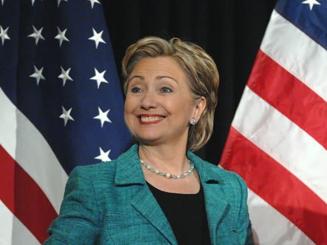 Hillary Clinton steht vor zwei US-Flaggen.