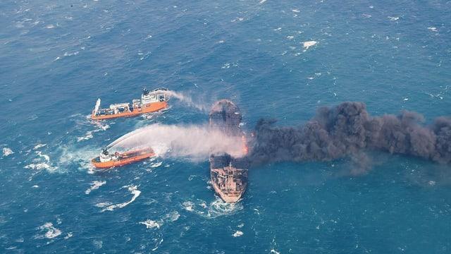 La nav-cisterna iranaisa «Sanchi» che arda. E dus bastiments ch'emprovan da stizzar.