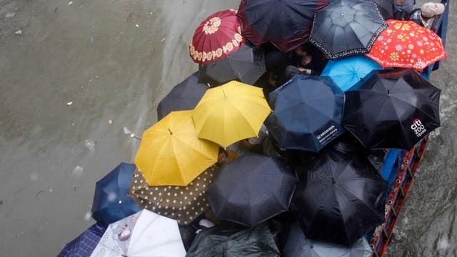 Ein Boot von oben, bunte Schirme sind zu sehen.