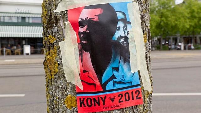 Ein Plakat mit dem Kopf von Rebellenführer Joseph Kony ist mit grossen Klebstreifen an einen Baum geklebt.