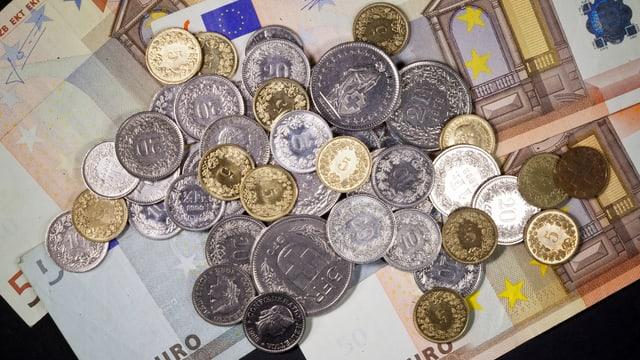 Schweizer-Franken-Münzen liegen auf Euro-Münzen.