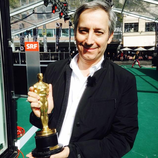 Heinz Schweizer hält einene Oscar.