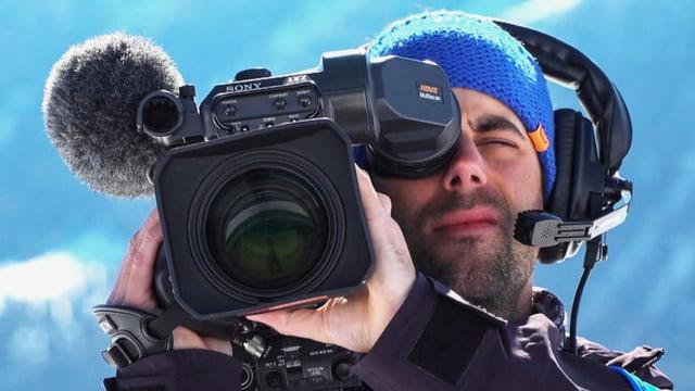 Kameramann mit Kamera auf der Schulter blickt frontal ins Bild.