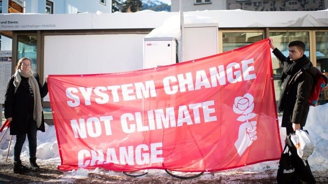 Protestierende am WEF 2019 in Davos halten ein Transparent in die Höhe.