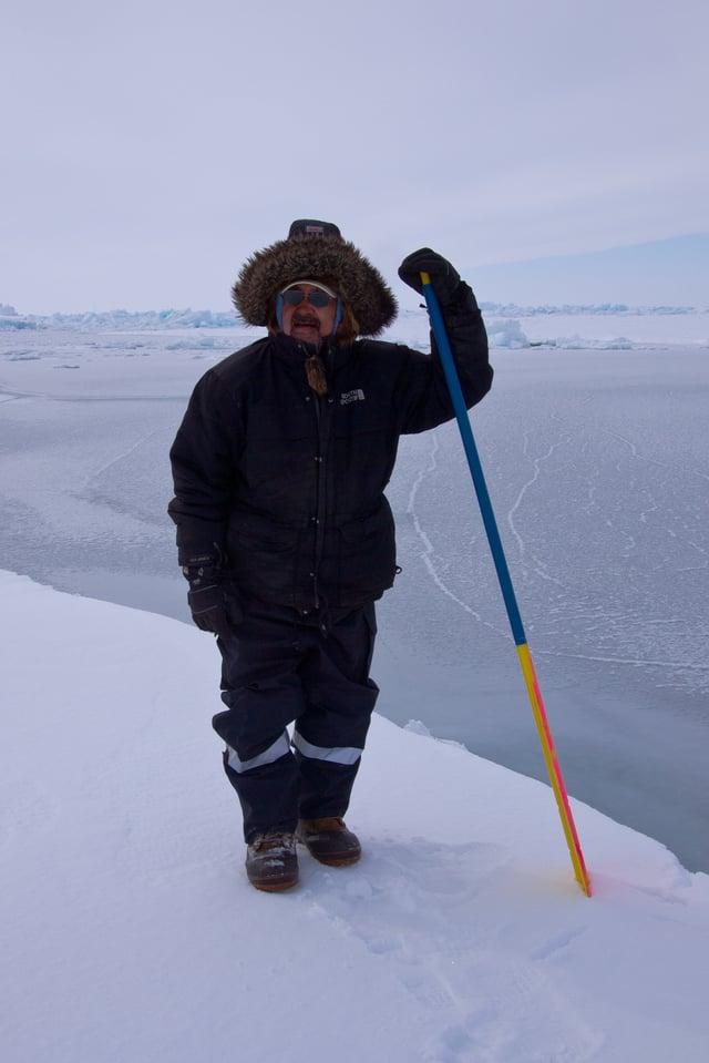 Ein Mann auf einer Eisfläche mit einem Stock in der Hand.