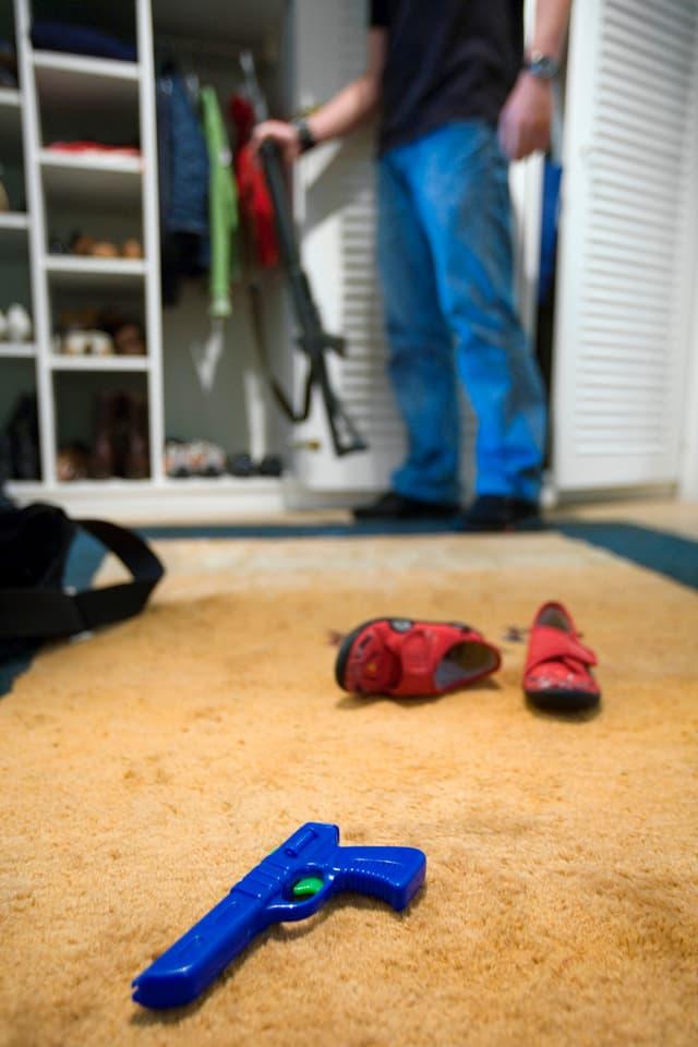 Ein Mann stellt sein Sturmgewehr in den Kleiderschrank, im Vordergrund liegen Kinderschuhe und eine Spielzeugpistole (2006).