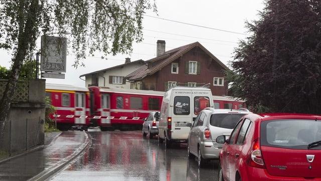 Autos che spetgan davant il passadi da tren a Malans.