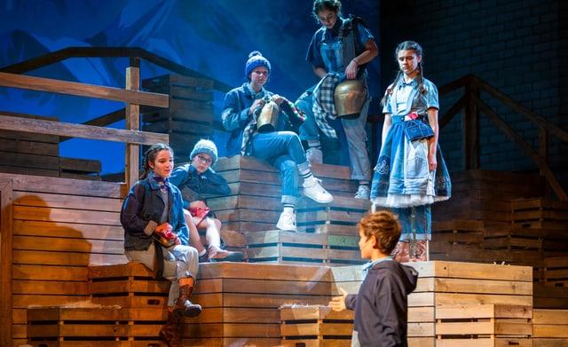 Fünf Kinder in traditioneller Kleidung sitzen und stehen auf einer Holztreppe.