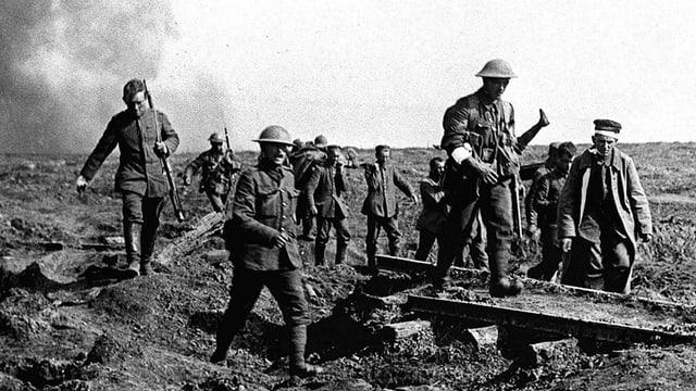 Soldaten schreiten über ein Schlachtfeld und tragen Verwundete.