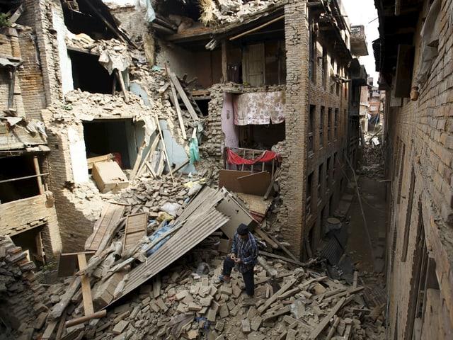 Eine enge gasse mit zum Teil eingestürzten Häusern.