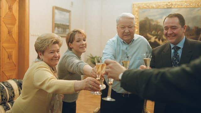 Eine Gruppe von Menschen, darunter Jelzin, stossen feierlich an mit einem Getränk.
