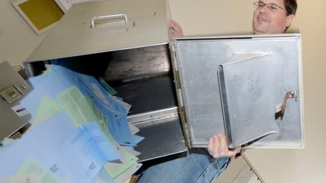 Im Wahlbüro leert ein Mann eine Wahlurne
