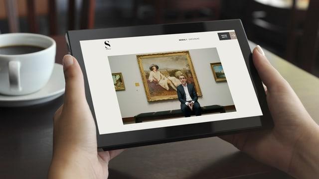 Zwei Hände halten ein Tablet, darauf ist ein Mann in einem Museum zu sehen.