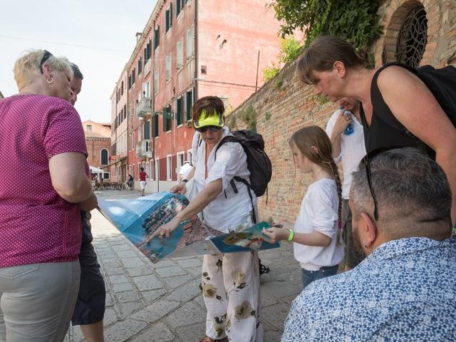 Eine Gruppe von Menschen schaut gemeinsam auf einen Stadtplan