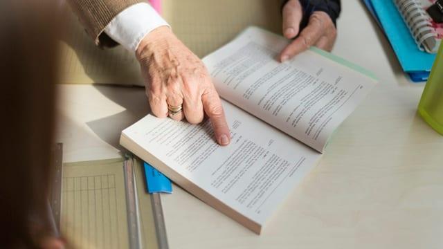 Hand zeigt auf offenes Gesetzesbuch