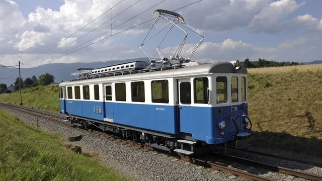 Eine Eisenbahn vor grünen Wiesen.