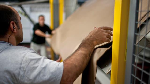 Mitarbeiter ziehen an einer Maschine Isolationspapier auf.