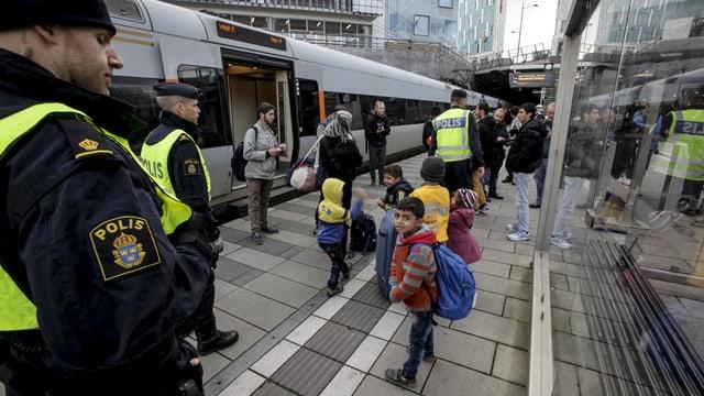 Schwedische Polizisten und eine Gruppe Migranten neben einem Zug.