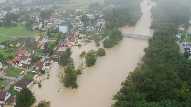 Brauner voller Fluss, Siedlungen rechts sind überschwemmt.