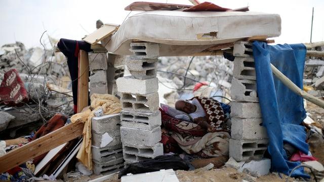 Ein Mann liegt unter einem Unterstand inmitten von Trümmern.