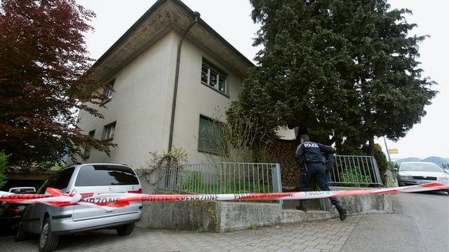 Ein Haus, davor ein rotes Absperrband und ein Polizeist, der ins Haus geht.