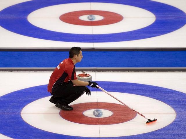 Marc Pfister auf dem Eis mit dem Besen.