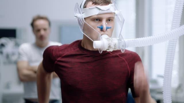 Ein junger Mann rennt auf dem Laufband beim Arzt. Er trägt eine Sauerstoffmaske.