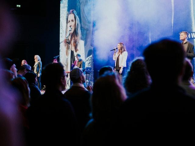 Publikum vor Bühne, darauf eine Leadsängerin vor LED-Screen