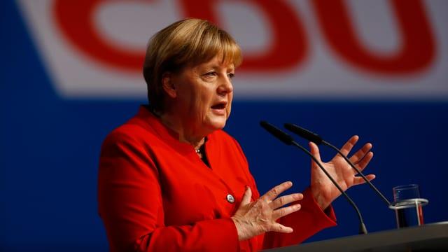 Merkel am Rednerpult vor einem grossen CDU-Logo.