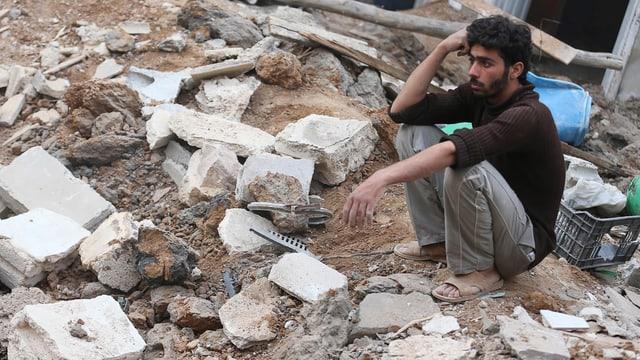 Ein Mann sitzt auf Trümmern