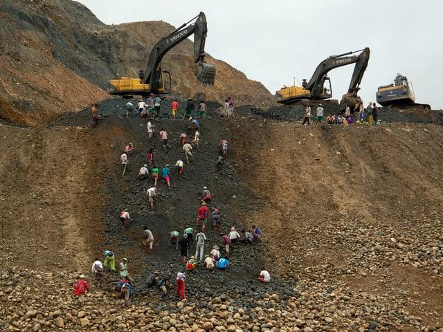 Jadesammler an einem Hang vor einer Mine.