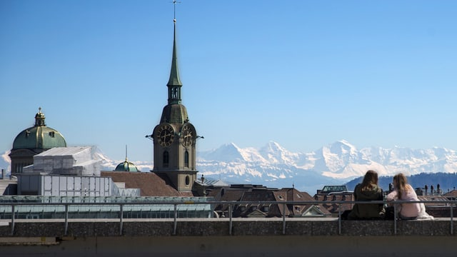 zwei Frauen neben Kirche, im Hintergrund die Berner Alpen.