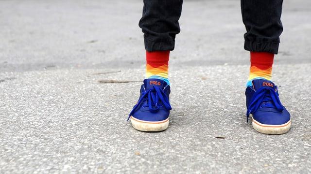 Beine in Traingshosen, Socken in Regenbogenfarben und blaue Turnschuhe.