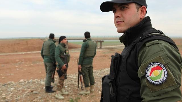 Vier irakisch-kurdische Kräfte, bewaffnet und in Uniform, stehen in der Nähe einer Brücke.