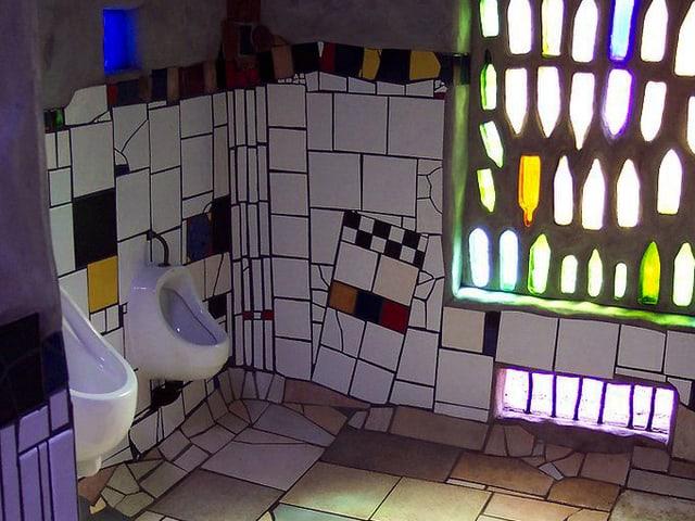 Toilette mit zwei Pissoirs mit bunten Wänden und einer Wand, in die ganze Flaschen eingelassen sind.