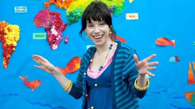 Eine lachende Frau steht vor einer Weltkarte, die Hände ausgestreckt.