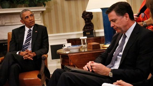 Barack Obama (links) sitzt schräg gegenüber von James Comey (rechts), der den Kopf gesenkt hat.