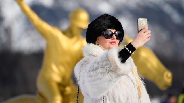 Eine Frau in Pelz macht ein Selfie.