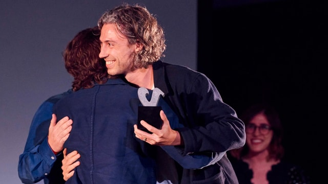 Kris Lüdi umarmt jemanden auf der Bühne und hält den dunkel gehaltenen Award in der Hand.