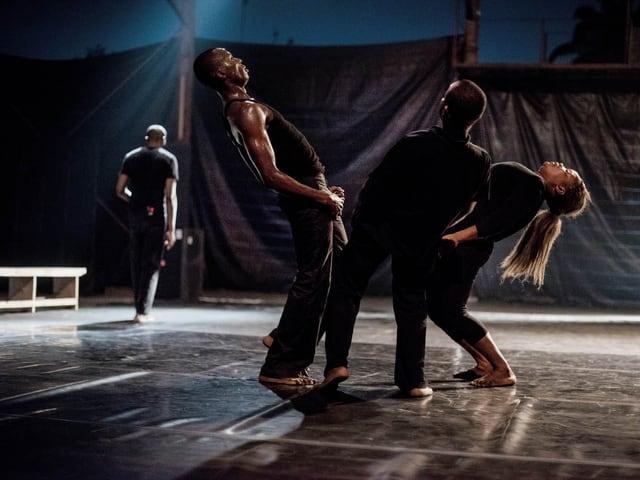 Eine Gruppe Tänzer stehen in einem Kreis, und biegen ihre Körper stark zurück.