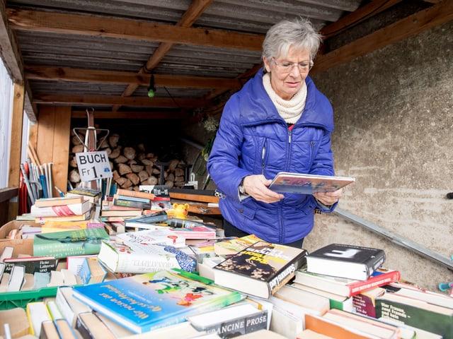 Margrit Bischofberger bestückt den Bücherwagen. Hier können Leute Bücher für einen Franken erstehen.