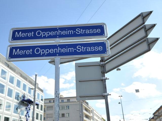 """Zwei Strassenschilder, beide mit der Aufschrift """"Meret Oppenheim-Strasse"""" direkt übereinander."""