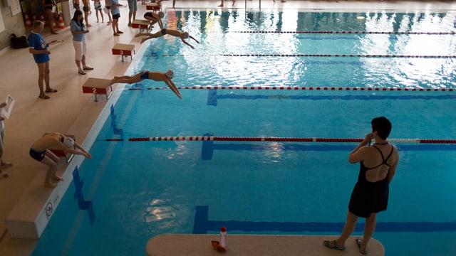 Kinder springen ins Schwimmbassin unter Aufsicht einer Schwimmlehrerin