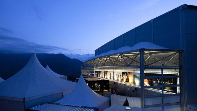 Blick auf den Konzertsaal, an dem unterschiedliche Veranstaltungen angeschlagen sind, vor der Alpen-Kulisse.